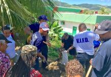 Residents gather at the Tutu fire station Monday morning for sandbag distribution.